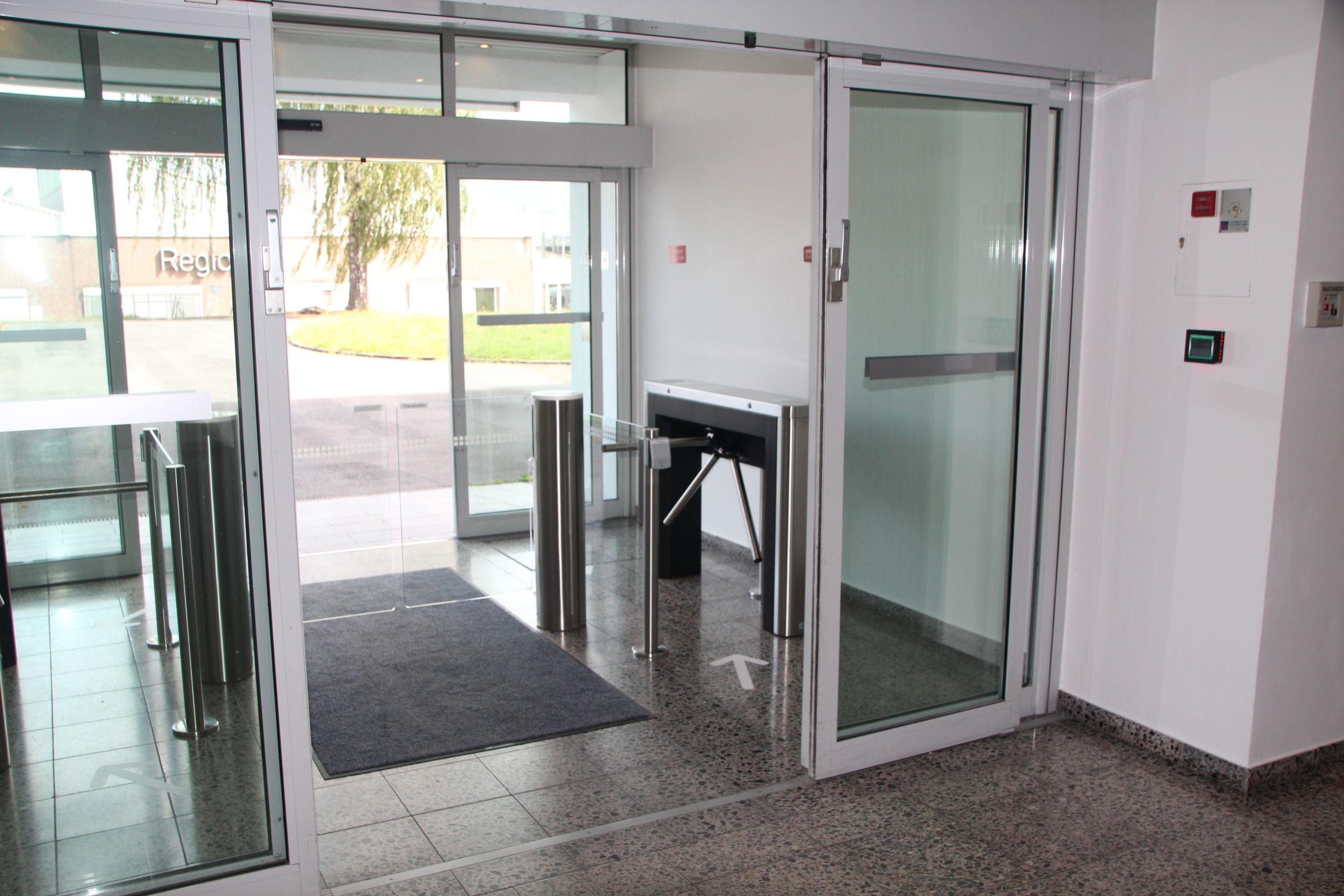 Drehsperren vom Typ TriLane 2 und zwei Schwenktüren vom Typ AccessLane sichern den Zugang zum Verwaltungsgebäude